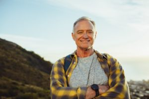 a retired person smiling with dental implant in Phoenix while on a hike